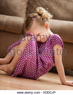 Shy girl (2-3) slitting on floor - Stock Photo