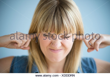 Woman blocking ears with fingers - Stock Photo