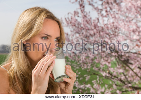Germany, North Rhine Westphalia, Young woman with glass of milk - Stock Photo