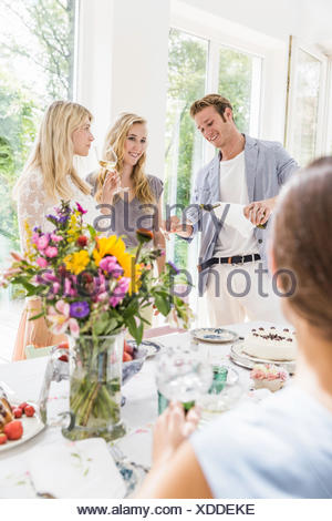 Young man pouring champagne for family at birthday party - Stock Photo