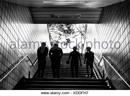 Rear View Of Silhouette People Walking On Staircase In Subway - Stock Photo
