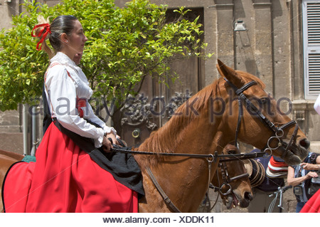 Woman riding a horse while wearing a traditional costume at the Cavalcata Sarda parade in Sassari, Sardinia, Italy, Europe - Stock Photo