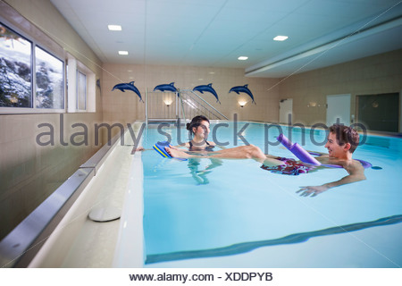 Patient and physiotherapist during underwater therapy - Stock Photo
