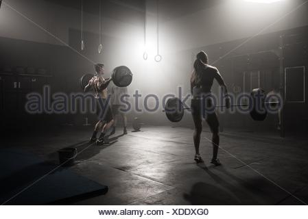 Man and woman lifting barbells in gym, rear view - Stock Photo