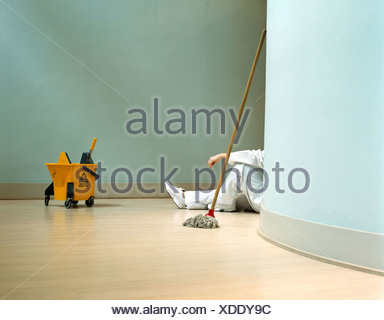 Cleaner relaxing in office - Stock Photo
