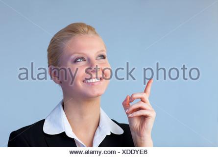 Happy Businesswoman pointing upwards - Stock Photo