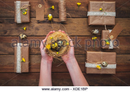 Wrapped gifts and girls hands holding a nest with easter eggs stock wrapped gifts and girls hands holding a nest with easter eggs stock photo negle Image collections