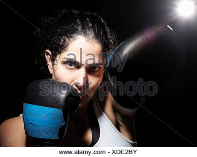 Portrait of female boxer against black background - Stock Photo