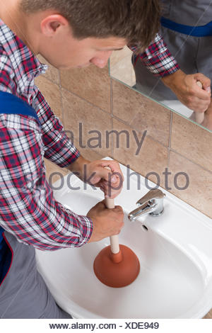 Plumber Using Plunger In Bathroom Sink - Stock Photo