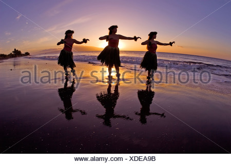 Three hula dancers are silhouetted by a setting sun at Olowalu, Maui. - Stock Photo