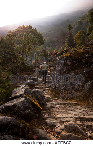 An unladen male trekker ascends a stone staircase to Lukla, Nepal. - Stock Photo