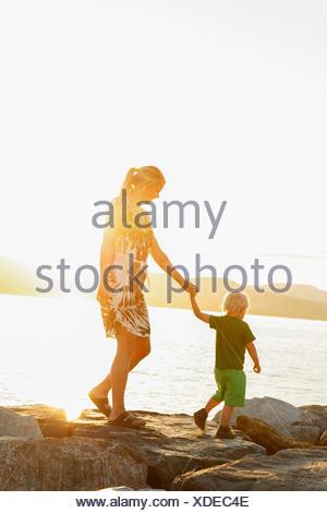 France, Provence-Alpes-Cote d´Azur, Saint Tropez, Woman walking with son along rocky coast at sunset - Stock Photo