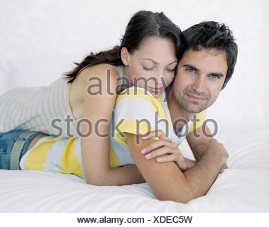 A couple lying on a bed - Stock Photo