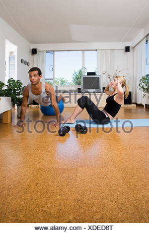 Young couple exercise at home, performing sit-ups and push-ups, Vancouver, British Columbia - Stock Photo