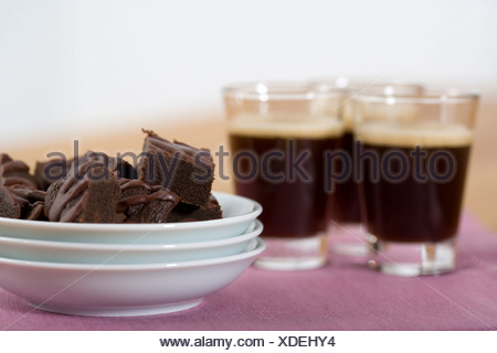 Three glasses of coffee next to a bowl with cookies - Stock Photo