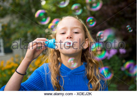 Girl blowing bubbles in garden - Stock Photo