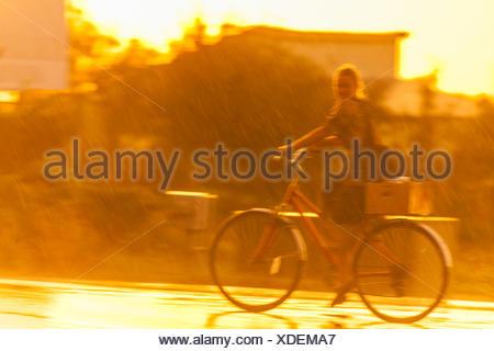 An Amish girl bikes in the rain on Route 23 near Churchtown, Pennsylvania. - Stock Photo