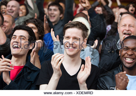 Fans clapping at football match - Stock Photo