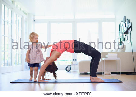 Mid adult mother practicing yoga with curious toddler daughter - Stock Photo