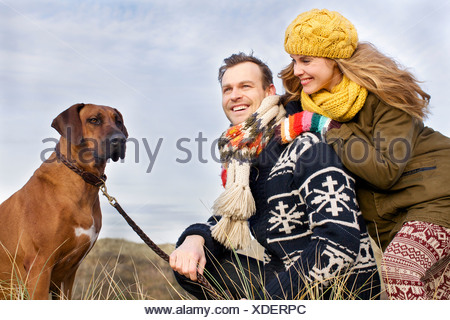 Smiling mid adult couple and dog at coast - Stock Photo