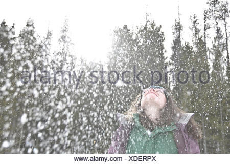 Woman in the snow throwing her head back and laughing - Stock Photo