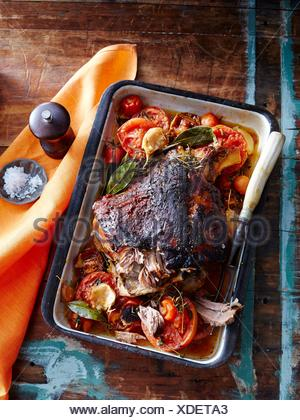 Slow roasted lamb with tomato and garlic crust - Stock Photo