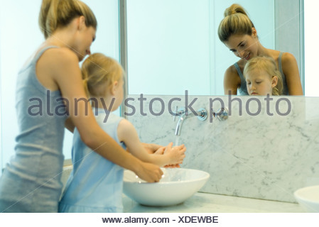 Woman helping little girl wash hands in bathroom sink - Stock Photo