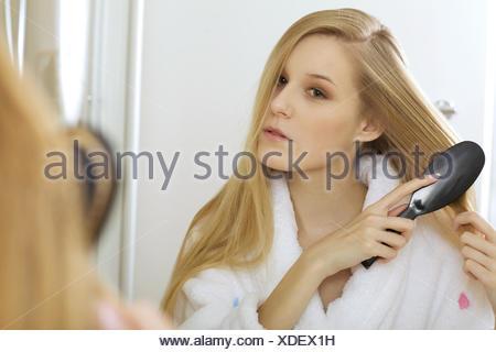 Woman brushing hair - Stock Photo