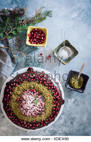 Christmas chocolate cake decorated with pomegranate seeds and pistachio accompanied by three small bowls and pine tree branches. - Stock Photo