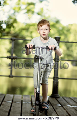 Portrait of little boy with push scooter standing on footbridge in a park - Stock Photo
