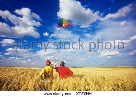 Couple in wheat field on Perrault Farm near Ponteix, Saskatchewan, Canada. - Stock Photo