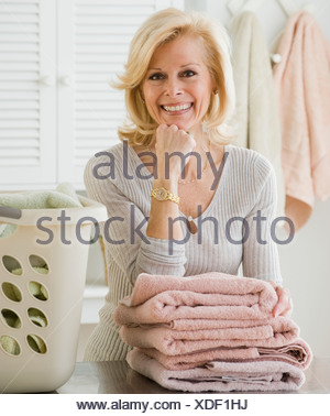 Senior woman leaning on folded towels - Stock Photo