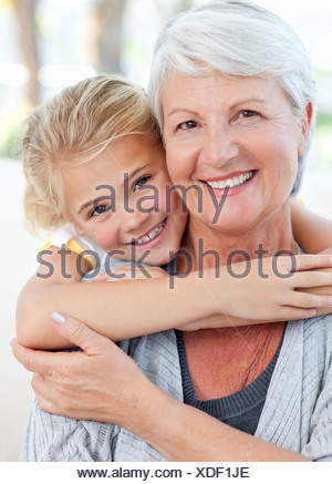 Lovely little girl with her grandmother looking at the camera - Stock Photo
