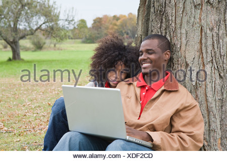 Couple looking at laptop outside - Stock Photo