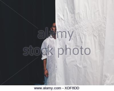 Portrait Of Young Man Standing Behind Curtain - Stock Photo