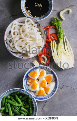 Ingredients for cooking stir fry udon noodles, green beans, sliced paprika, boiled eggs, soy sauce with sesame seeds in traditional bowls with wooden  - Stock Photo