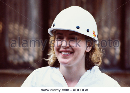 UK Industry. Woman wearing hard hat. - Stock Photo