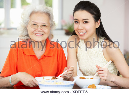 Chinese Mother And Adult Daughter Eating Meal Together - Stock Photo