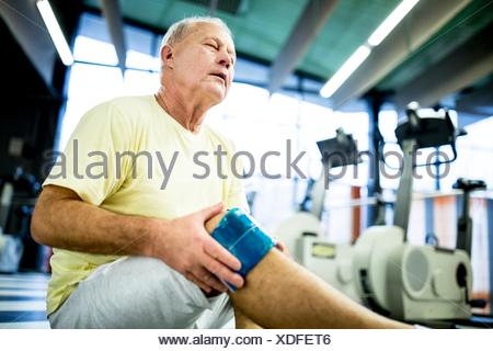 PROPERTY RELEASED. MODEL RELEASED. Senior man holding ice pack on injured knee in gym. - Stock Photo