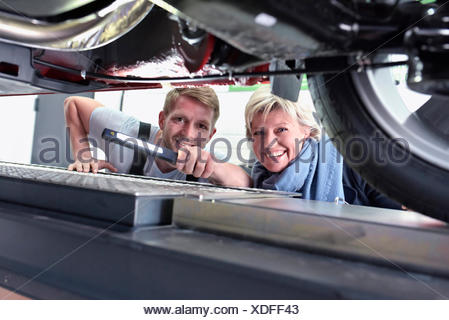 Portrait of smiling car mechanic with client in workshop at car - Stock Photo