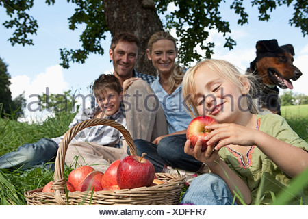 Germany, Bavaria, Altenthann,Girl with basket of apples, family with dog in background - Stock Photo