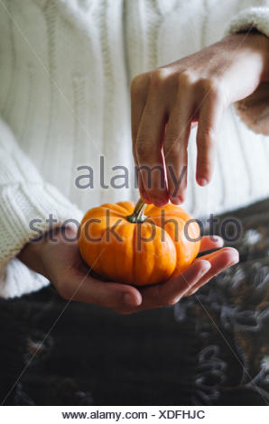 Midsection Of Person Holding Pumpkin - Stock Photo