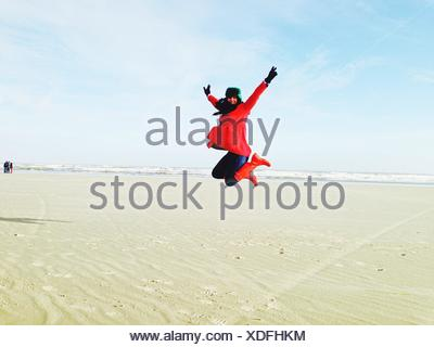 Portrait Of Woman Jumping At Beach Against Sky - Stock Photo