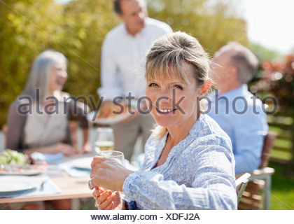 Portrait of smiling senior woman enjoying lunch with friends at sunny table - Stock Photo