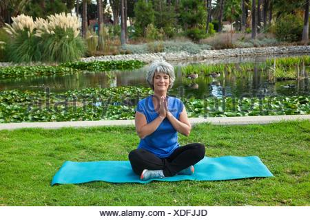 Mature woman sitting on mat in park, meditating - Stock Photo