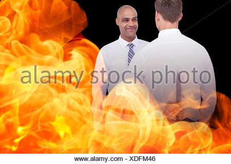 Composite image of businessman holding knife behind his back - Stock Photo