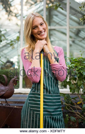 Portrait of beautiful gardener with work tool against greenhouse - Stock Photo