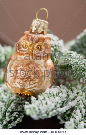 Christmas tree ornament: owl on snow-covered fir branch - - Stock Photo