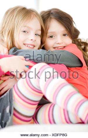 Close up of sisters hugging - Stock Photo