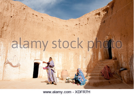 Two Berber women dressed in traditional costume in a cave dwelling, Matmata, Tunisia, Southern Tunisia, Maghreb, North Africa - Stock Photo